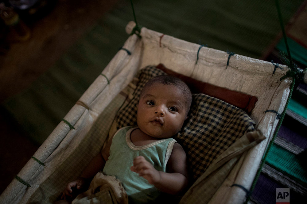 """""""M"""" sits in her shelter, uninterested in her baby boy who had awoken from his sleep, in Kutupalong refugee camp in Bangladesh, June 26, 2018. (AP Photo/Wong Maye-E)"""
