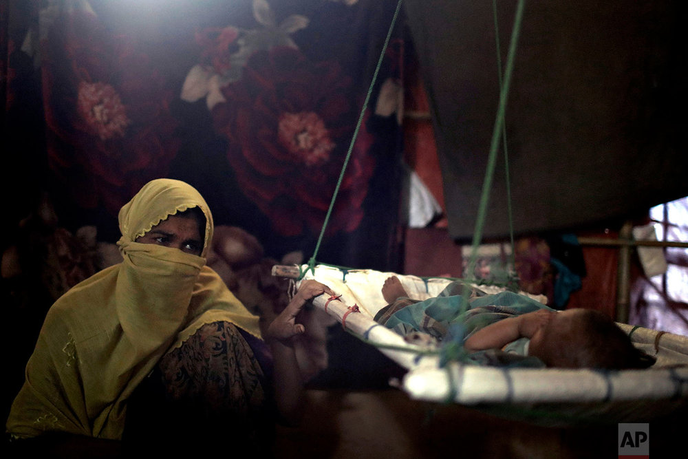 """""""M"""" sits in her shelter, rocking her baby boy who had awoken from his sleep, in Kutupalong refugee camp in Bangladesh,June 26, 2018. (AP Photo/Wong Maye-E)"""