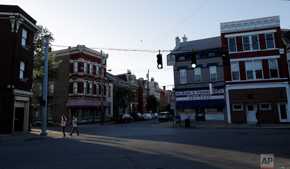 Two women cross a street in Covington, Ky. (AP Photo/Gregory Bull)