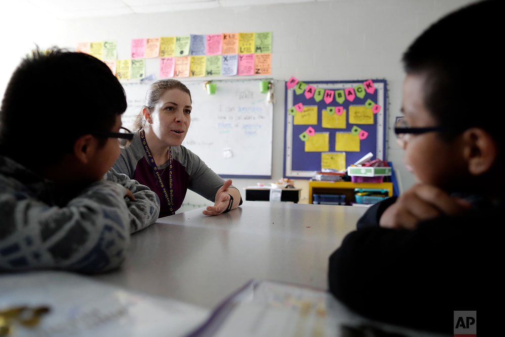 School social worker Kerry McHugh talks to children at John G. Carlisle Elementary School in Covington, Ky. (AP Photo/Gregory Bull)