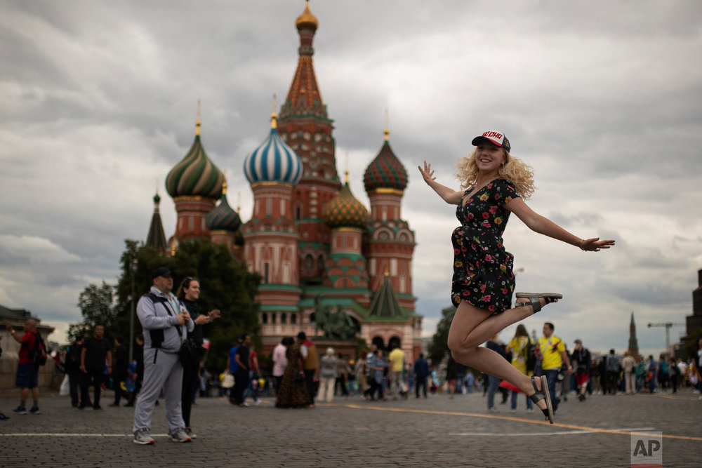 A woman jumps as she poses for a photograph at the Red Square during the 2018 soccer World Cup in Moscow, Russia on Tuesday, July 3, 2018. (AP Photo/Francisco Seco)