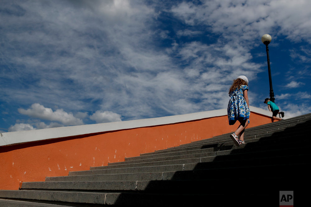 A girl walks up the stairs during the 2018 soccer World Cup in Nizhny Novgorod, Russia on Wednesday, July 4, 2018. (AP Photo/Natacha Pisarenko)
