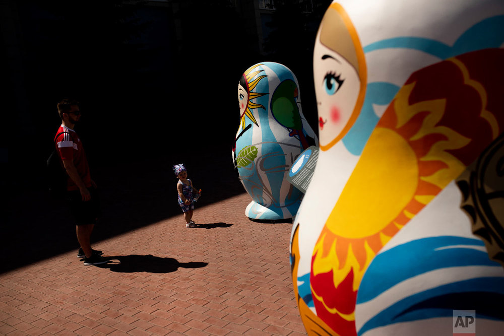 A man and a child stand next to oversize Russian Matryoshka dolls placed in a public park in Samara, Russia on Sunday, July 8, 2018. (AP Photo/Francisco Seco)