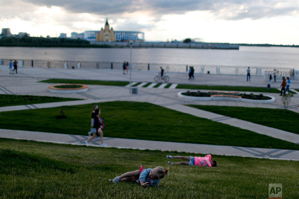 Girls roll down the grass in a park in front of the Nizhny Novgorod stadium during the 2018 soccer World Cup in Nizhny Novgorod, Russia on Thursday, July 5, 2018. (AP Photo/Natacha Pisarenko)