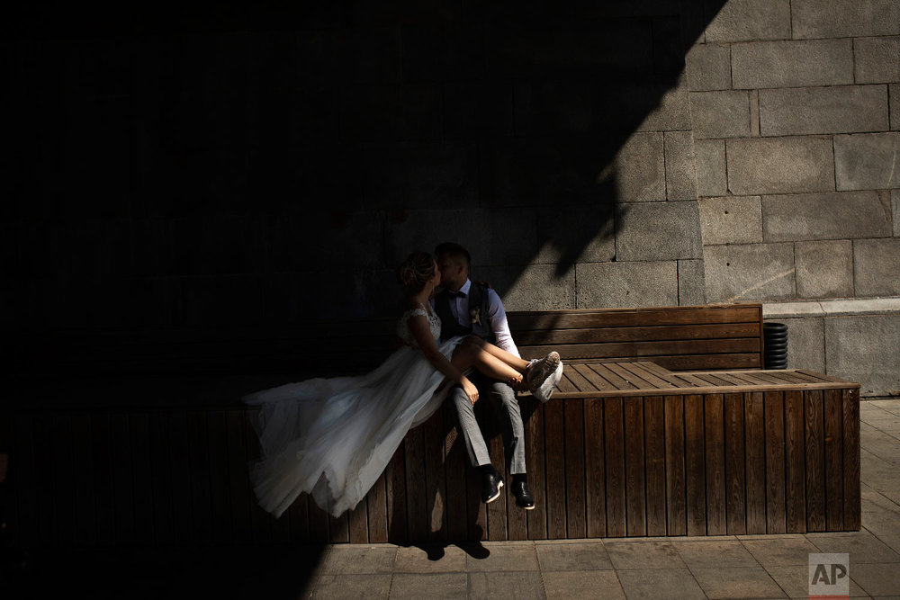 A newlywed couple pose during a photograph session under the Krymsky Bridge in Moscow, Russia during the 2018 soccer World Cup on Thursday, July 5, 2018. (AP Photo/Francisco Seco)