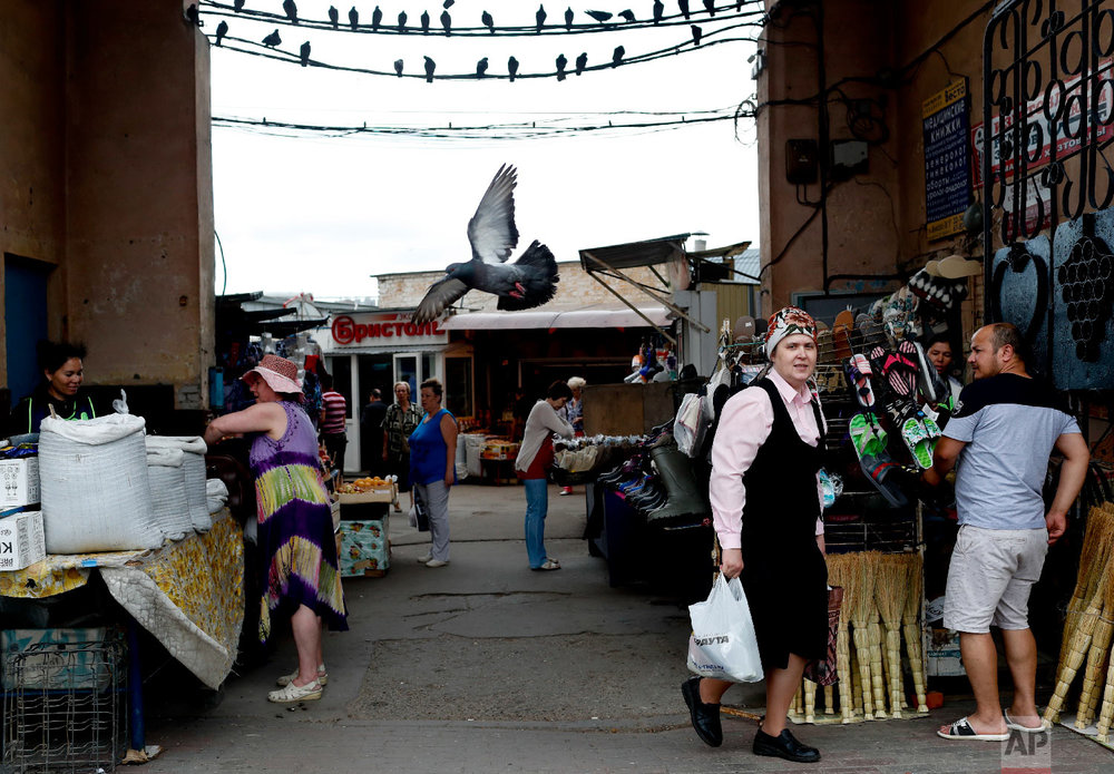 A woman walks out a market during the 2018 soccer World Cup in Nizhny Novgorod, Russia on Saturday, July 7, 2018. (AP Photo/Natacha Pisarenko)