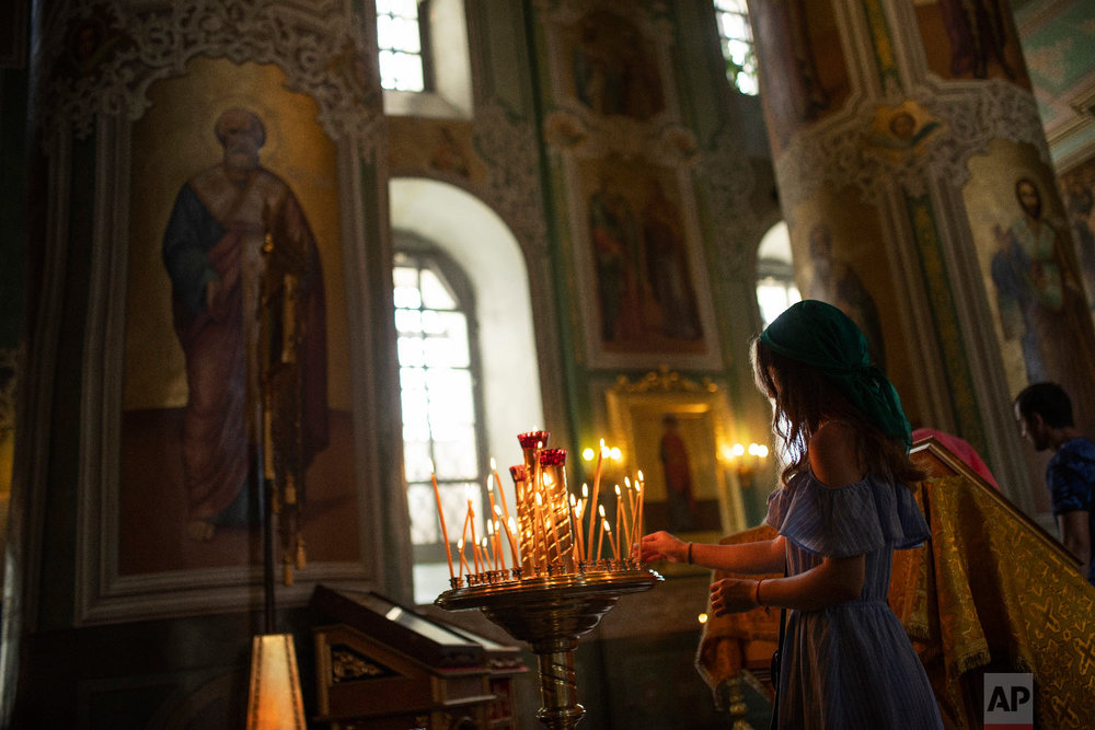 A woman lights a candle in the Annunciation Cathedral at the 2018 soccer World Cup in Kazan, Russia on Friday, July 6, 2018. (AP Photo/Francisco Seco)