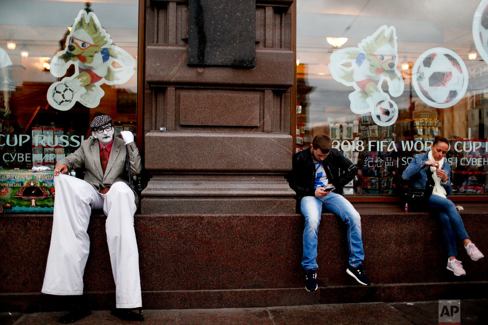 Residents and a street artist sit in a window shop during the 2018 soccer World Cup in St. Petersburg, Russia on Sunday, July 8, 2018. (AP Photo/Natacha Pisarenko)