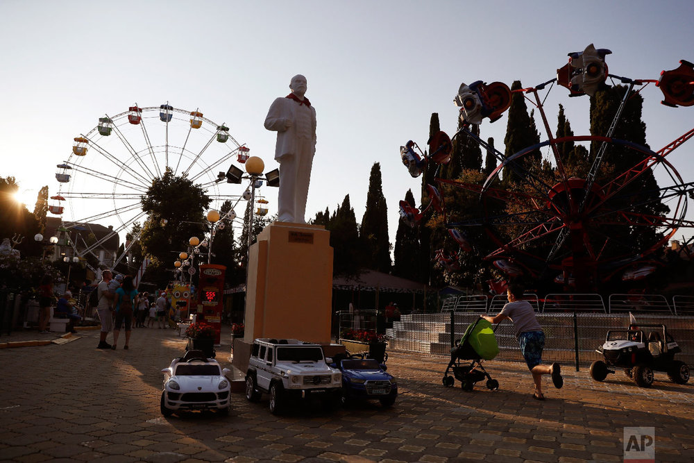 A boy pushes a stroller past a Lenin statue at an amusement park during the 2018 soccer World Cup in Sochi, Russia on Sunday, July 8, 2018. (AP Photo/Pavel Golovkin)