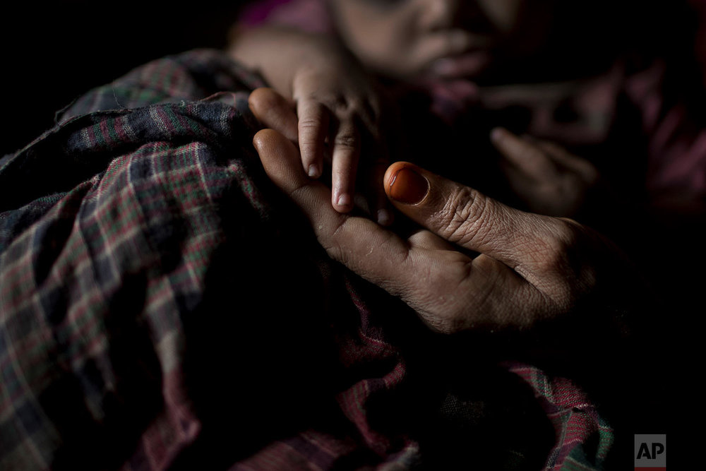 """""""S"""" holds her baby boy's hand as she sits in her shelter in Balukhali refugee camp in Bangladesh, June 25, 2018. (AP Photo/Wong Maye-E)"""