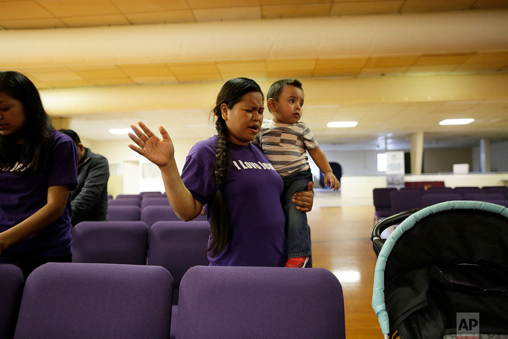 Alma Vazquez prays as she holds one of her five children at the Tabernacle Bible Church in Fairfield, Ohio. (AP Photo/Gregory Bull)