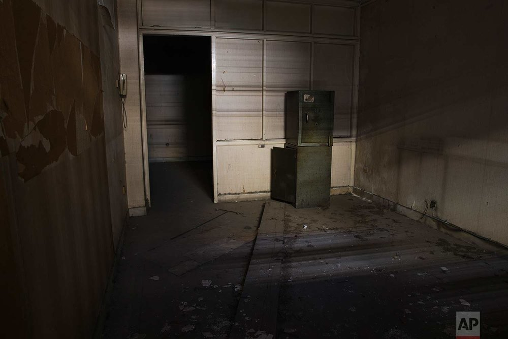 Two safes stand in a room inside a 7-story block off central Athens' gritty Omonia Square, that has been untenanted since a now-defunct farm cooperative fund left years ago. (AP Photo/Petros Giannakouris)