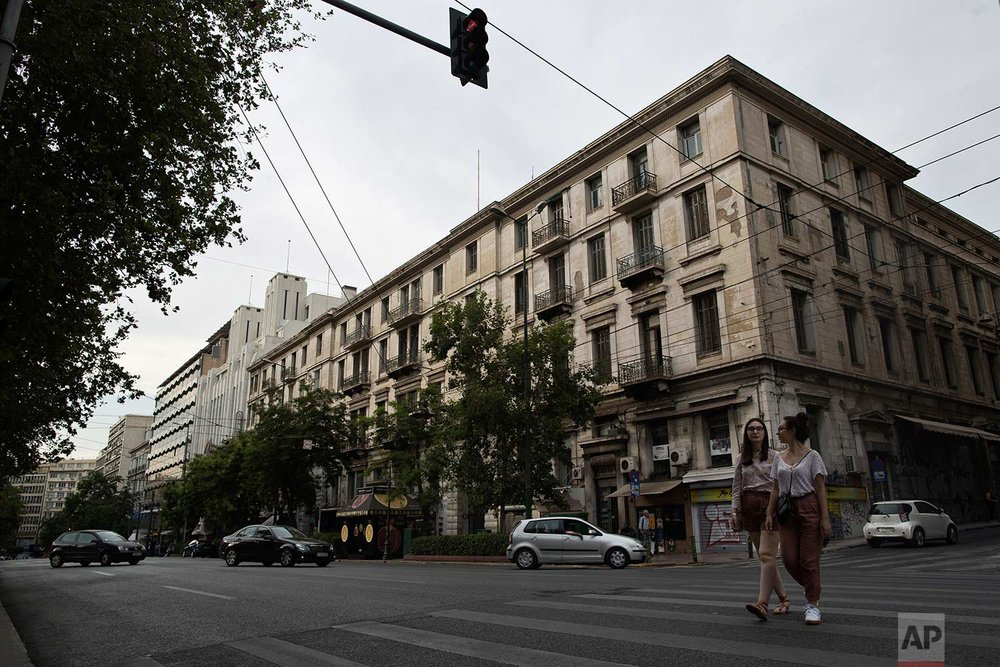 Pedestrians walk in front of one of Athens' few substantial late 19th century buildings to survive brutal postwar development. (AP Photo/Petros Giannakouris)