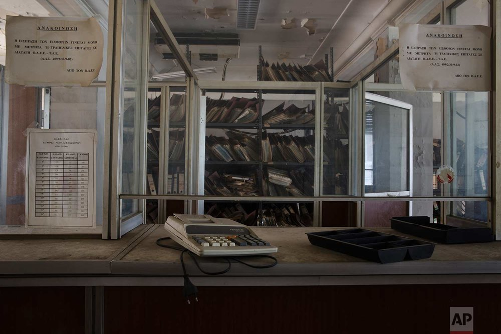A calculator on a booth in front of shelves of paper files in a 2,600-square meter listed building from 1955, formerly used by a commerce fund company. (AP Photo/Petros Giannakouris)