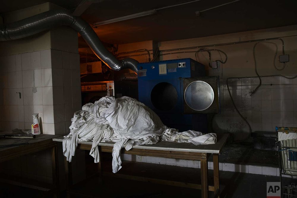 White bed sheets are stacked in front of a washing machine in the former Hesperia Hotel, which closed abruptly during Greece's financial crisis. (AP Photo/Petros Giannakouris)
