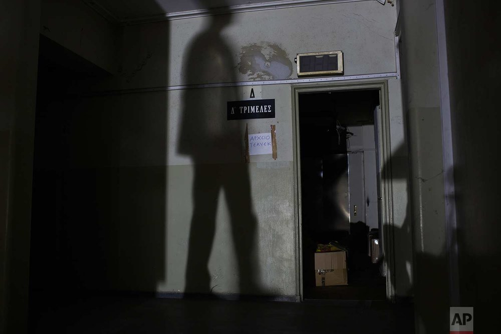 "A man's shadow appears next to a sign reading ""Three-member Court"" in the former Ambassadeur hotel in Athens. (AP Photo/Petros Giannakouris)"