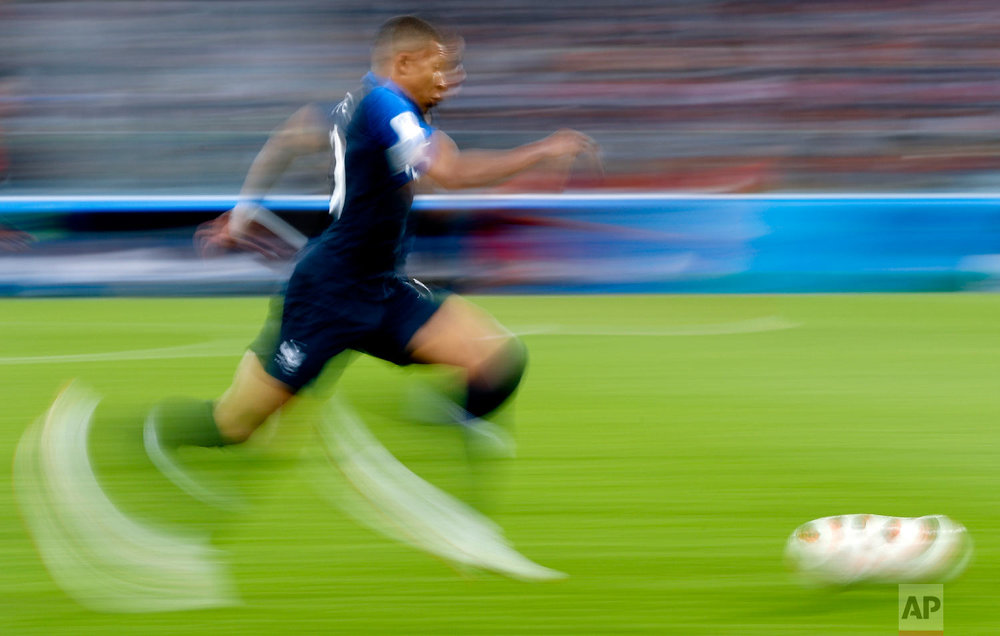 In this photo taken with slow shutter speed France's Kylian Mbappe runs with the ball during the semifinal match between France and Belgium at the 2018 soccer World Cup in the St. Petersburg Stadium, in St. Petersburg, Russia, Tuesday, July 10, 2018. (AP Photo/Petr David Josek)