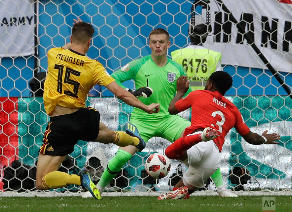 Belgium's Thomas Meunier, left, scores his side's opening goal against England goalkeeper Jordan Pickford as England's Danny Rose tries to defend during the third place match between England and Belgium at the 2018 soccer World Cup in the St. Petersburg Stadium in St. Petersburg, Russia, Saturday, July 14, 2018. (AP Photo/Petr David Josek)