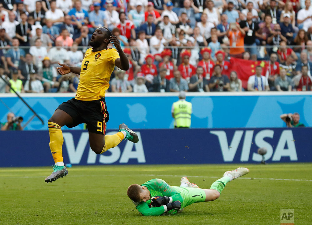 England goalkeeper Jordan Pickford stops a scoring attempt by Belgium's Romelu Lukaku during the third place match between England and Belgium at the 2018 soccer World Cup in the St. Petersburg Stadium in St. Petersburg, Russia, Saturday, July 14, 2018. (AP Photo/Petr David Josek)