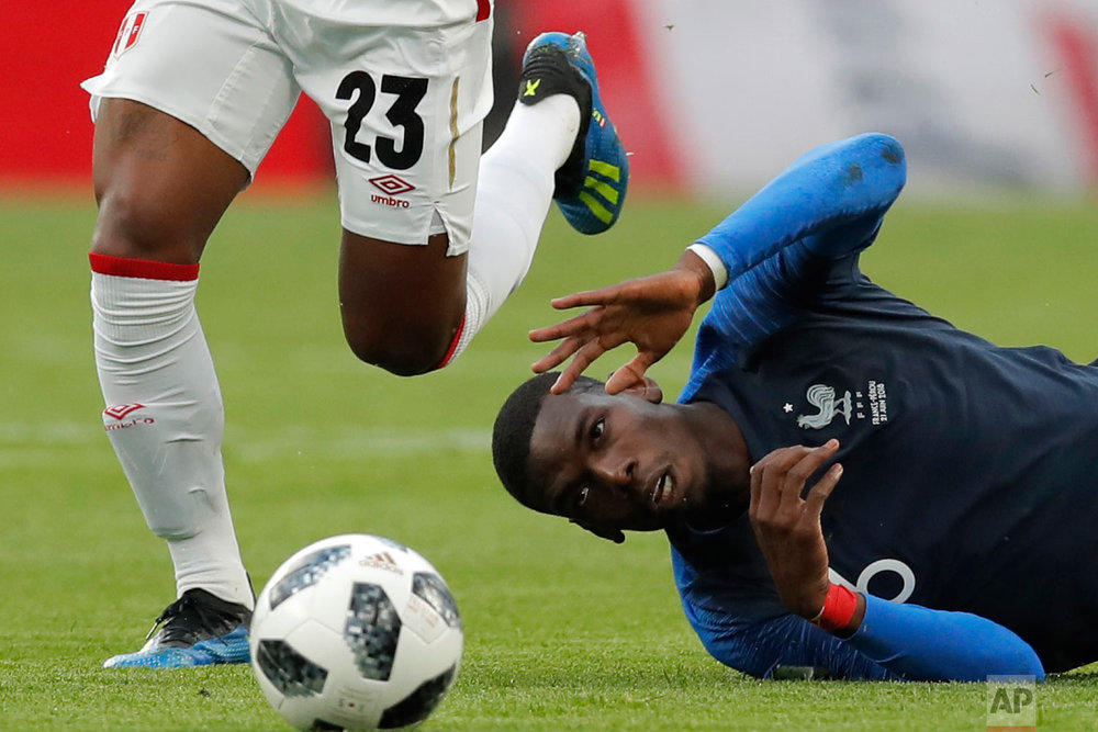 France's Paul Pogbais tackled by Peru's Pedro Aquino during the group C match between France and Peru at the 2018 soccer World Cup in the Yekaterinburg Arena in Yekaterinburg, Russia on June 21, 2018. (AP Photo/Vadim Ghirda)
