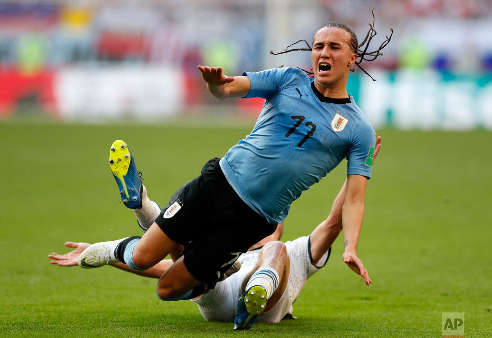 Russia's Igor Smolnikov stops Uruguay's Diego Laxalt during the group A match between Uruguay and Russia at the 2018 soccer World Cup at the Samara Arena in Samara, Russia on June 25, 2018. (AP Photo/Rebecca Blackwell)