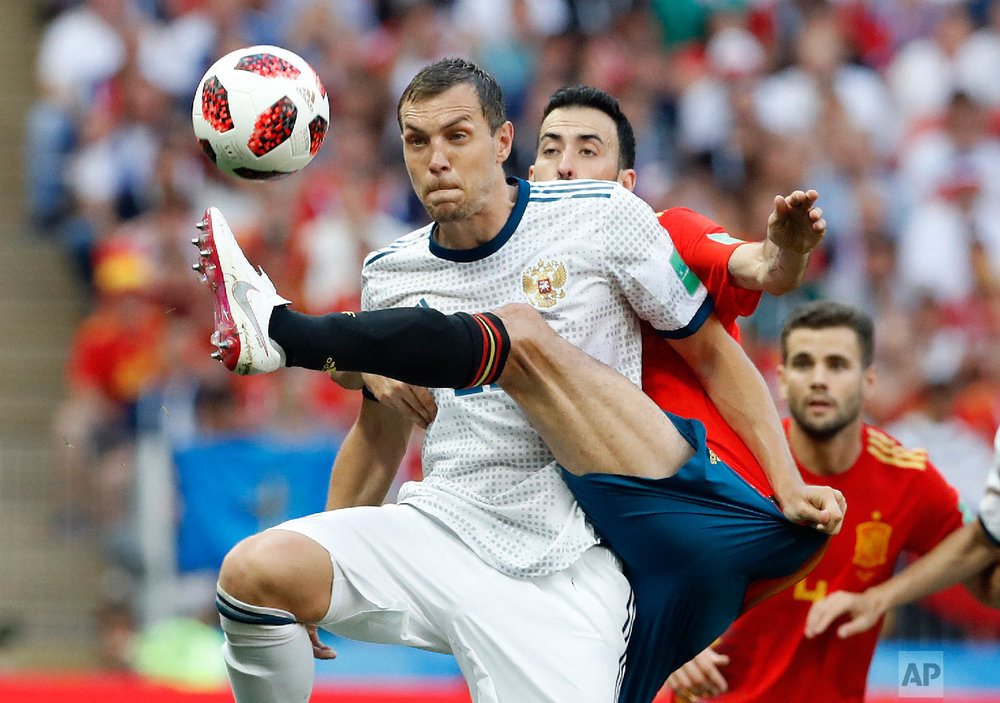 Russia's Artyom Dzyuba, front , and Spain's Sergio Busquets challenge for the ball during the round of 16 match between Spain and Russia at the 2018 soccer World Cup at the Luzhniki Stadium in Moscow, Russia on July 1, 2018. (AP Photo/Antonio Calanni)
