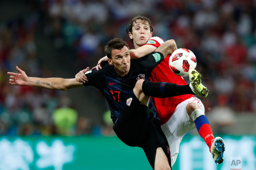 Croatia's Mario Mandzukic, left, challenges for the ball with Russia's Mario Fernandes during the quarterfinal match between Russia and Croatia at the 2018 soccer World Cup in the Fisht Stadium, in Sochi, Russia on July 7, 2018. (AP Photo/Rebecca Blackwell)