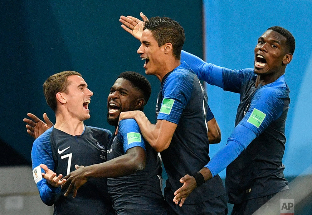 France's Samuel Umtiti, second from left, is congratulated by his teammates France's Antoine Griezmann, Raphael Varane and Paul Pogba, from left, after scoring the opening goal during the semifinal match between France and Belgium at the 2018 soccer World Cup in the St. Petersburg Stadium in St. Petersburg, Russia on July 10, 2018. (AP Photo/Martin Meissner)