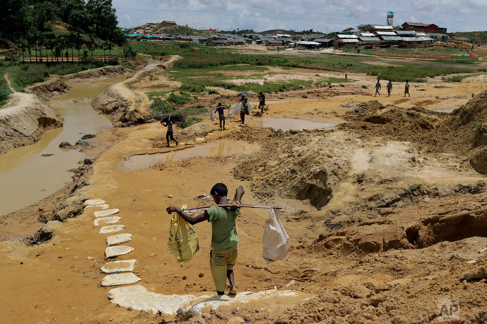 In this Thursday, June 28, 2018, photo, Rohingya refugees carry construction material to an extended area of Kutupalong refugee camp in Bangladesh where some refugees living in areas considered at risk of landslides and flooding were relocated to. (AP Photo/Wong Maye-E)
