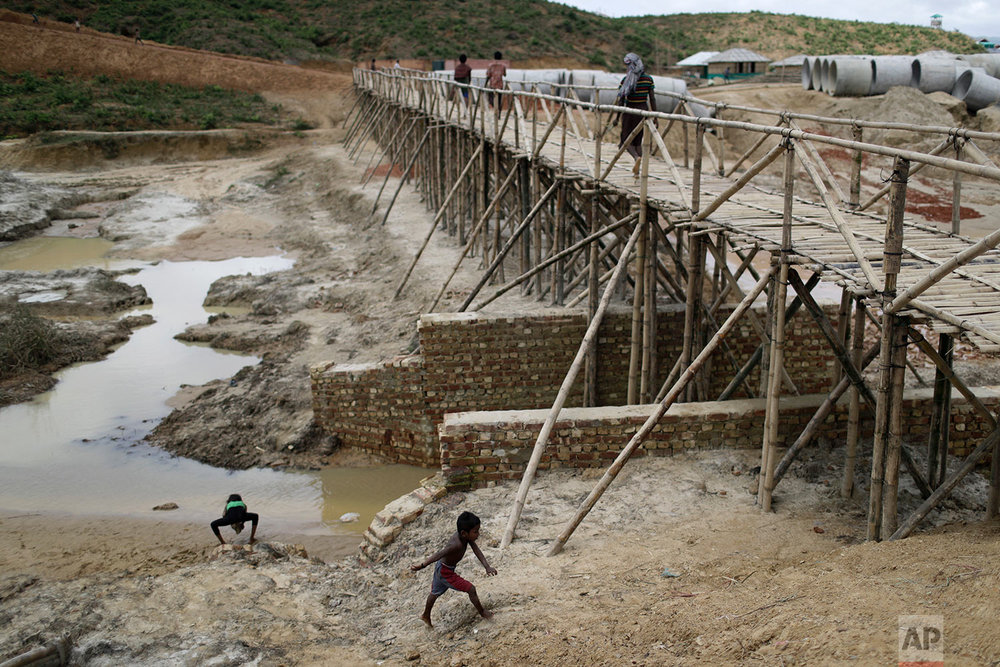 In this Thursday, June 28, 2018, photo, Rohingya refugees cross a newly built bridge in the extended area of Kutupalong refugee camp in Bangladesh where some refugees living in areas considered at risk of landslides and flooding were relocated to. (AP Photo/Wong Maye-E)