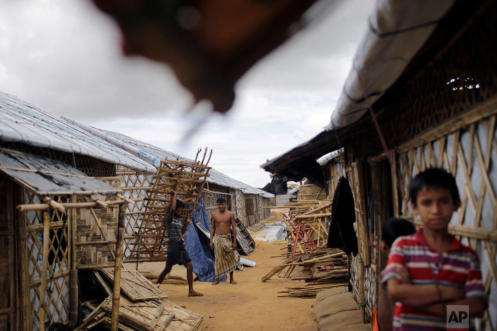 In this Thursday, June 28, 2018, photo, Rohingya refugees carry construction material through huts built in an extended area of Kutupalong refugee camp in Bangladesh where some refugees living in areas considered at risk of landslides and flooding were relocated to.  (AP Photo/Wong Maye-E)