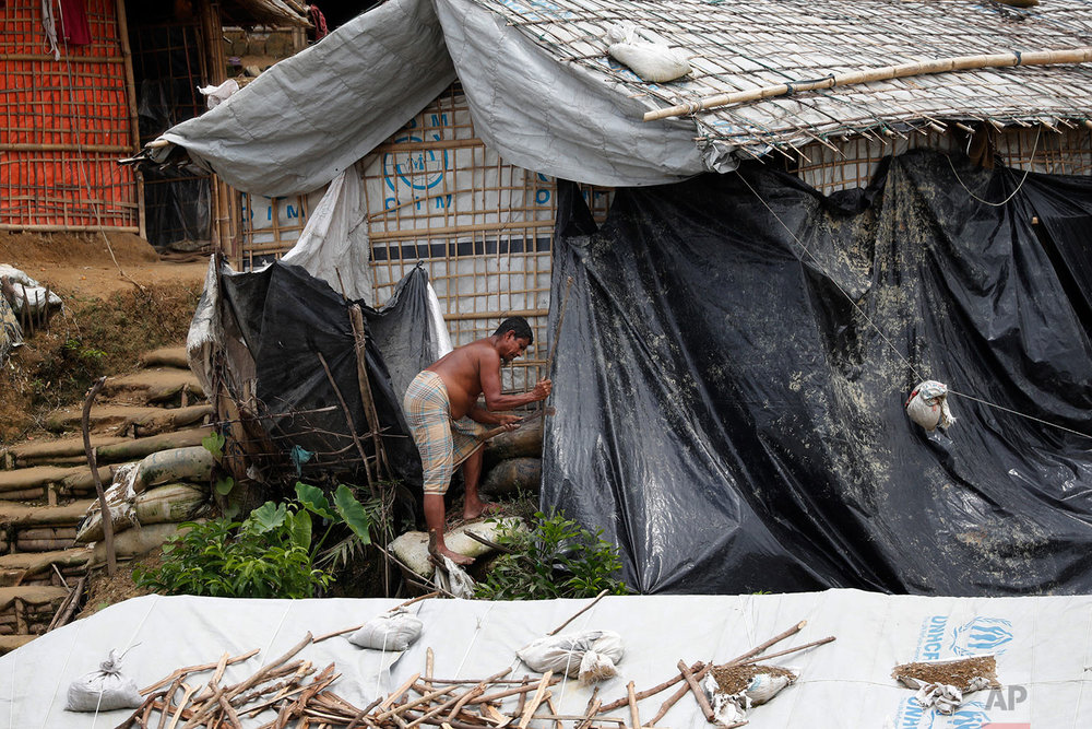 In this Wednesday, June 27, 2018, photo, a man covers his shelter with waterproof tarp as he prepares for the monsoon season in Chakmarkul refugee camp, Bangladesh. (AP Photo/Wong Maye-E)