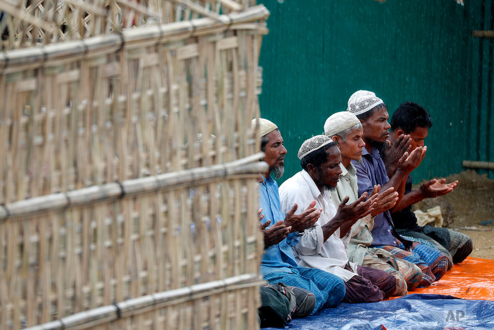 In this Thursday, June 28, 2018, photo, Rohingya Muslim men offer prayers in the rain at an extended area of Kutupalong refugee camp in Bangladesh where some refugees living in areas considered at risk of landslides and flooding were relocated to. (AP Photo/Wong Maye-E)
