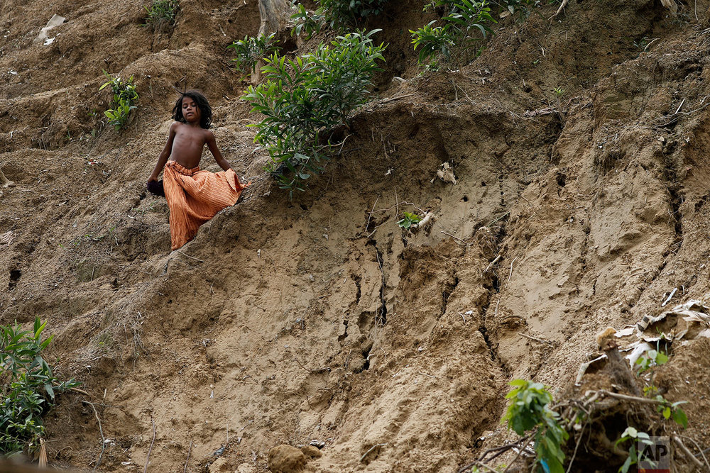 In this Wednesday, June 27, 2018, photo, a young girl slides down the side of a muddy hill where a landslide which destroyed eight shelters occured in Chakmarkul refugee camp, Bangladesh. (AP Photo/Wong Maye-E)