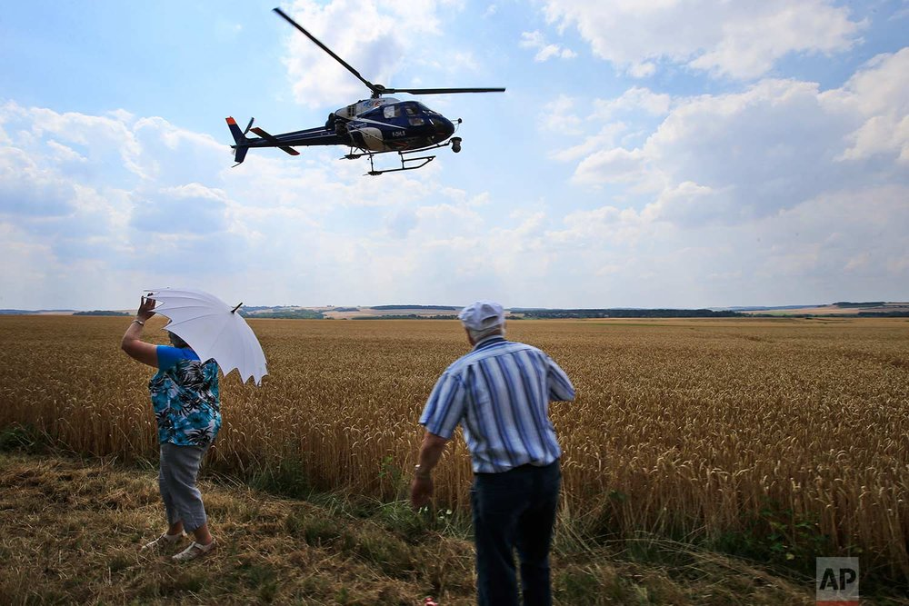 Spectators turn their backs to passing riders to wave to the helicopter with the live TV feed during the eight stage of the Tour de France cycling race over 181 kilometers (112.5 miles) with start in Dreux and finish in Amiens, France, Saturday, July 14, 2018. (AP Photo/Peter Dejong)