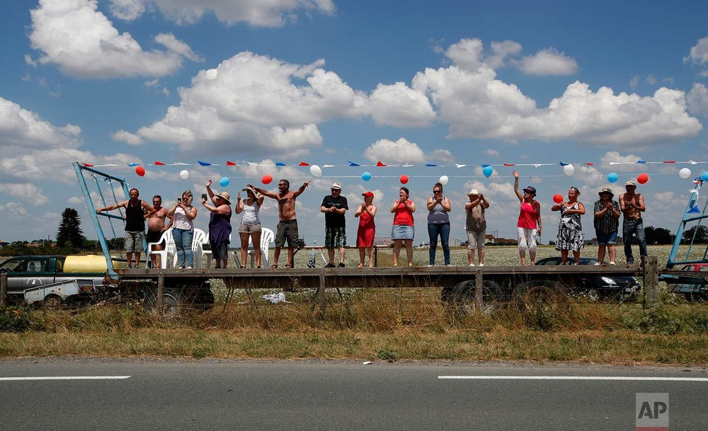 Spectators wait for the pack to pass during the first stage of the Tour de France cycling race over 201 kilometers (124.9 miles) with start in Noirmoutier-en-L'Ile and finish in Fontenay Le-Comte, France, Saturday, July 7, 2018. (AP Photo/Christophe Ena)