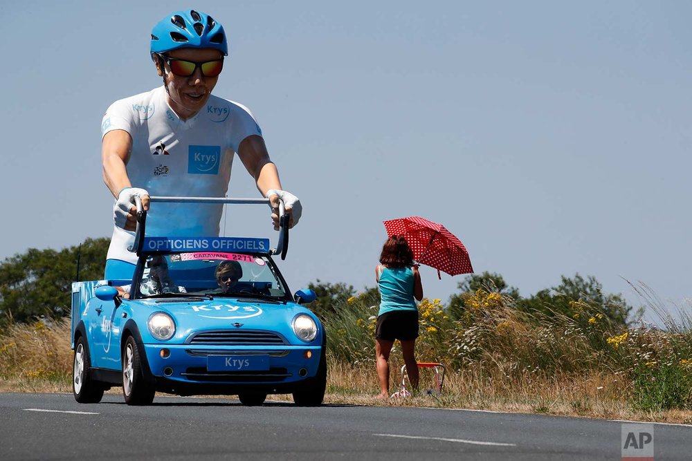 A vehicle of the sponsor's parade passes a spectator waiting for riders to pass during the third stage of the Tour de France cycling race, a team time trial over 35.5 kilometers (22 miles) with start and finish in Cholet, France, Monday, July 9, 2018. (AP Photo/Christophe Ena)