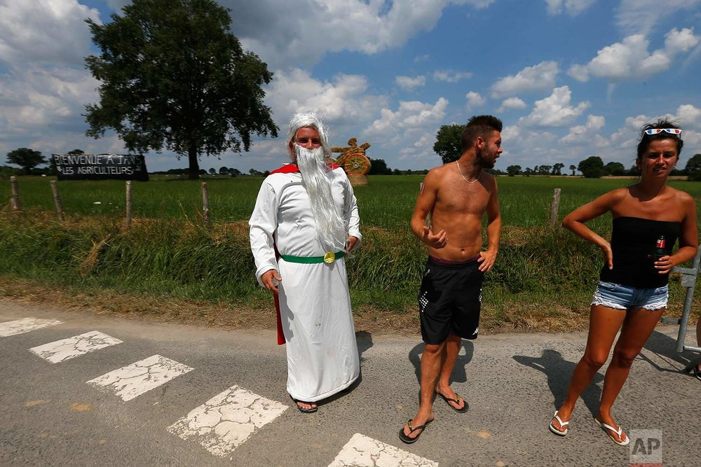 Spectators wait for the riders to pass during the fourth stage of the Tour de France cycling race over 195 kilometers (121 miles) with start in La Baule and finish in Sarzeau, France, Tuesday, July 10, 2018. (AP Photo/Peter Dejong)