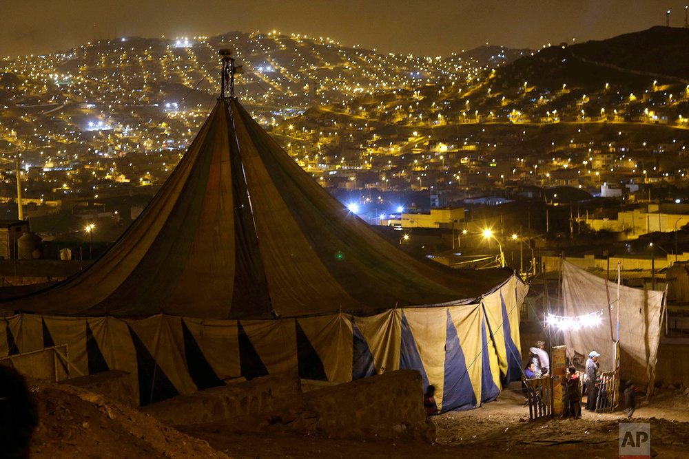 Homes in the Puente Piedra shantytown light up the landscape surrounding the Tony Perejil circus on the outskirts of Lima, Peru. (AP Photo/Martin Mejia)