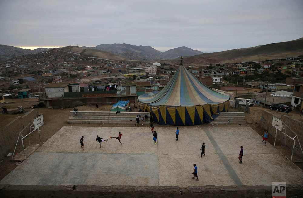 Youths play soccer next to the Tony Perejil circus tent set up in the shantytown of Puente Piedra on the outskirts of Lima, Peru, July 8, 2018. (AP Photo/Martin Mejia)