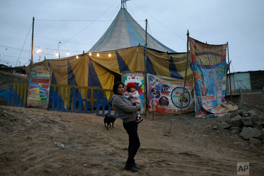 A woman with her baby waits for one of her daughters to arrive before entering the Tony Perejil circus tent, set up in the shantytown of Puente Piedra on the outskirts of Lima, Peru, July 8, 2018. Tickets cost 6 Soles (2 dollars) for adults, and are half price for children. (AP Photo/Martin Mejia)