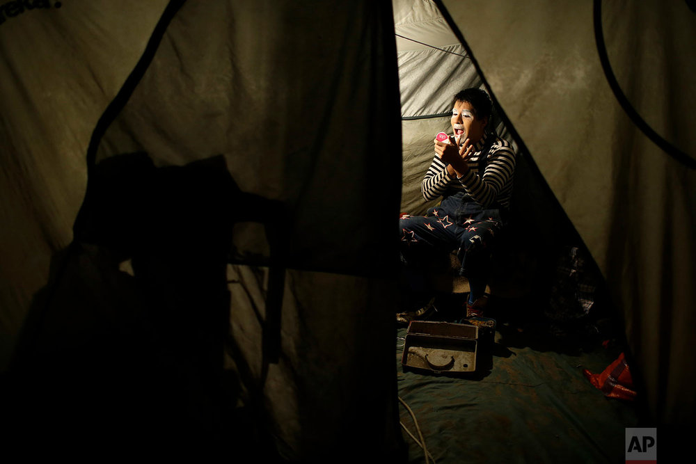 "Santiago Astopilco puts on his clown make-up to play the part of ""Vaguito"" inside his tent at the Tony Perejil circus set up in the shantytown of Puente Piedra on the outskirts of Lima, Peru, July 8, 2018. (AP Photo/Martin Mejia)"