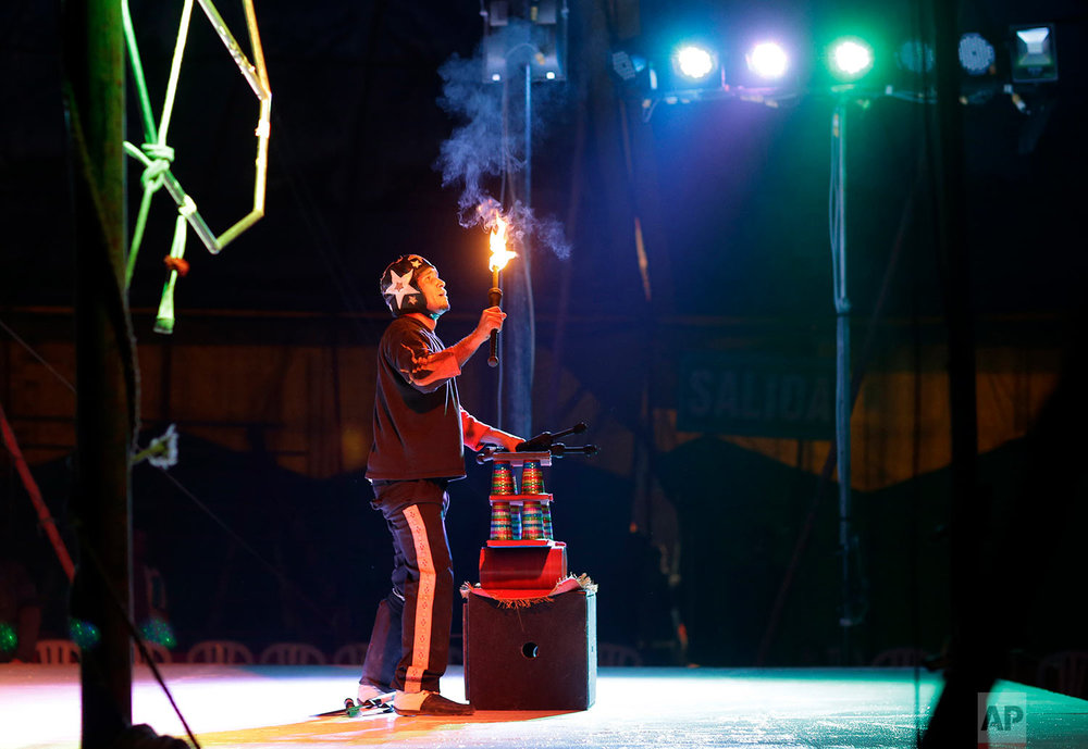 Juggler Alfredo Cordova performs with fire at the International Circus set up in the shantytown of Pro on the outskirts of in Lima, Peru, July 20, 2018. (AP Photo/Martin Mejia)
