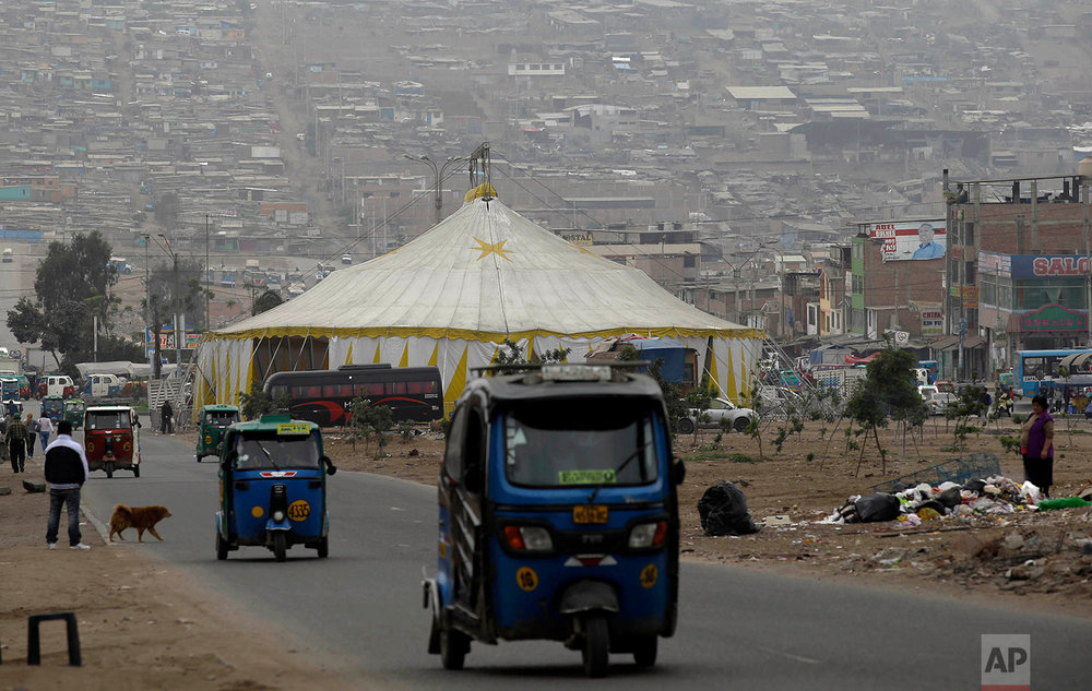 Moto-taxi drivers pass La Panfila Circus tent set up in the shantytown of Villa El Salvador in Lima, Peru, July 13, 2018. (AP Photo/Martin Mejia)
