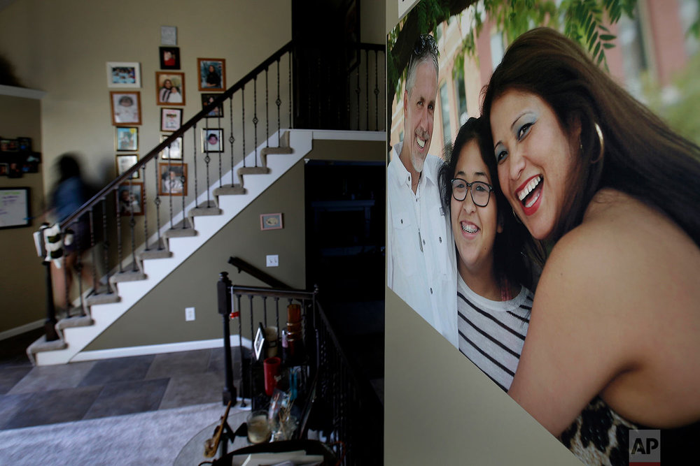 Jennifer Tadeo-Uscanga, 17, walks down a staircase lined with family photos at the Kansas City, Mo., home she once shared with her mother, Letty Stegall. (AP Photo/Charlie Riedel)