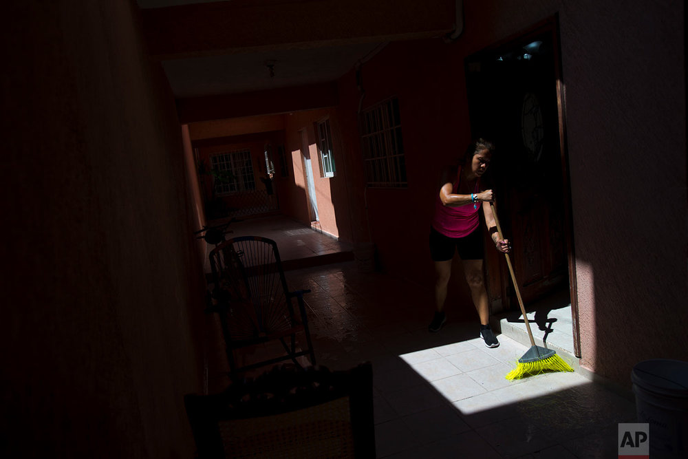 Letty Stegall sweeps the entryway to her parents' home in Boca Del Rio, Veracruz state, Mexico. (AP Photo/Rebecca Blackwell)