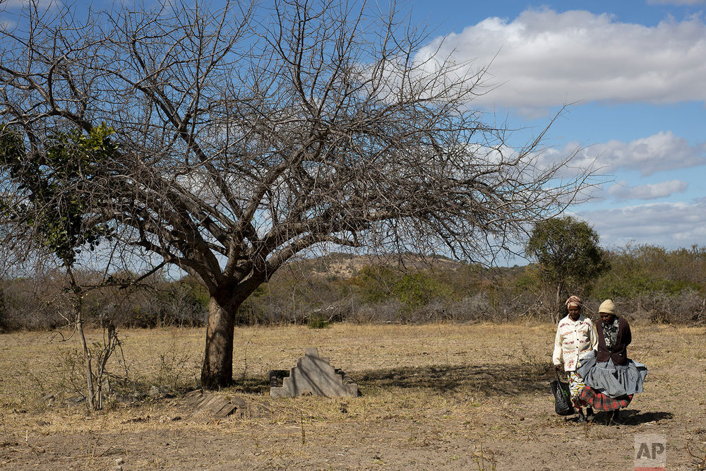 Ellis Ndlovu, 91, walks in Simbumbumbu, Zimbabwe, past the grave of her son Edwel. (AP Photo/Jerome Delay)