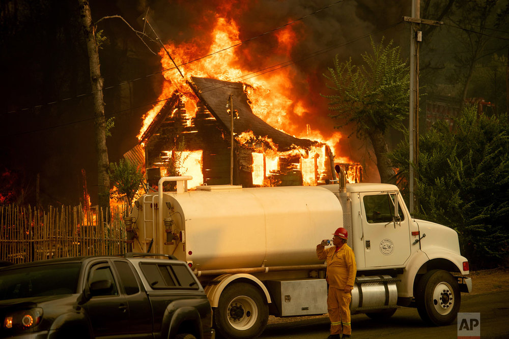 A water tender operator drinks a beverage after trying to save a home burning in Shasta, Calif., on Thursday, July 26, 2018. (AP Photo/Noah Berger)