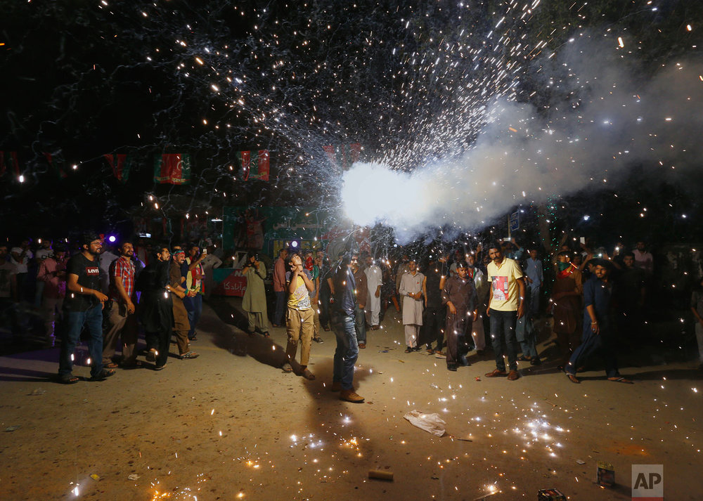 A supporter of Imran Khan, chief of the Tehreek-e-Insaf party, releases fireworks to celebrate projected unofficial results announced by television channels indicating their candidates' success in the parliamentary elections in Islamabad, Pakistan, Thursday, July 26, 2018. With election officials declaring the party of Imran Khan to be the winner of parliamentary balloting, the former cricket star turned Friday to forming a coalition government, since the party did not get an outright majority. (AP Photo/Anjum Naveed)