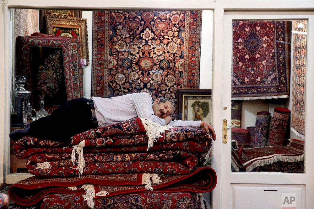 A carpet seller takes a nap at the carpet market in the old main Bazaar in Tehran, Iran, Monday, July 23, 2018. Iranians shrugged off the possibility that a bellicose exchange of words between President Donald Trump and his Iranian counterpart could escalate into military conflict, but expressed growing concern America's stepped-up sanctions could damage their fragile economy. (AP Photo/Ebrahim Noroozi)